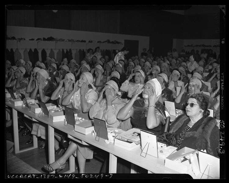 Audience of women applying makeup at lecture by beautician Manka Rubenstein in Los Angeles, Calif., circa 1950